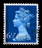 Postage stamp. UNITED KINGDOM - CIRCA 1990: An English Used First Class Postage Stamp printed in UNITED KINGDOM showing Portrait of Queen Elizabeth in blue royalty free illustration