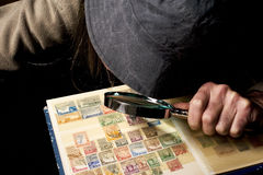 Postage stamp collector. A postage stamp collector watching his collection of stamps with a magnifying glass Royalty Free Stock Images