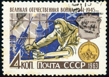 Postage stamp - medal For the defense of Leningrad. The woman works on a machine against the backdrop of city defenders and the medal `For the defense of stock illustration