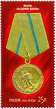Postage stamp - the medal `For defense of Odessa`. The image of a gold-colored medal and a yellow pad with blue and red stripes on a red background stock illustration