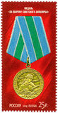 Postage stamp - the medal `For defense of Soviet Arctic`. Medal image of golden color and green-blue pads on a red background royalty free illustration
