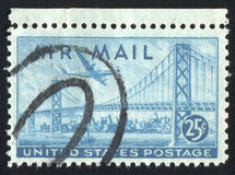Postage stamp. UNITED STATES - CIRCA 1947: stamp printed by United states, shows Plane over San Francisco-Oakland Bay Bridge, circa 1947 stock image