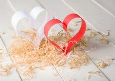 Postal al día de tarjeta del día de San Valentín Corazón blanco y rojo hecho de las tiras de papel Virutas de madera rizadas deco Foto de archivo libre de regalías