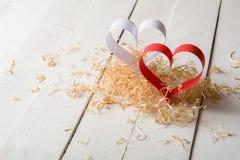 Postal al día de tarjeta del día de San Valentín Corazón blanco y rojo hecho de las tiras de papel Virutas de madera rizadas deco Fotos de archivo