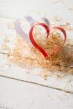Postal al día de tarjeta del día de San Valentín Corazón blanco y rojo hecho de las tiras de papel Virutas de madera rizadas deco Imagenes de archivo