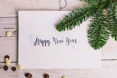 Postal con la enhorabuena y el chocolate, rama de árbol en el fondo de madera blanco deletreado Arte Gráfico Año Nuevo Imagen de archivo