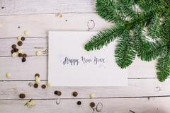 Postal con la enhorabuena y el chocolate, rama de árbol en el fondo de madera blanco deletreado Arte Gráfico Año Nuevo Fotografía de archivo