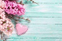 Postal con los jacintos rosados frescos y corazón decorativo en t Foto de archivo
