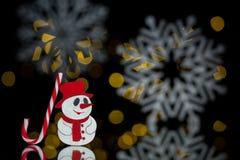 Postal del Año Nuevo con el muñeco de nieve del juguete, el bastón de caramelo y los copos de nieve; Imagenes de archivo