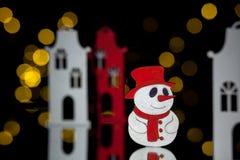 Postal del Año Nuevo con las casas y el muñeco de nieve del juguete; Foto de archivo libre de regalías