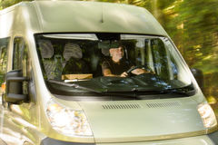 Postal delivery courier man drive cargo van. Postal delivery courier man driving cargo van delivering package Royalty Free Stock Photo