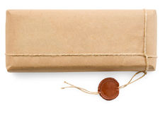 Postal parcel in coarse paper on white background Stock Photography