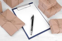 Postal parcels and envelopes and a form for filling with a pen on a wooden table. mail or delivery concept stock image