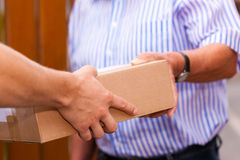 Postal service - delivery of a package. The postman is giving the package to the customer (only hands and package to be seen Stock Images