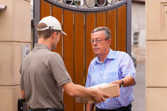 Postal service - delivery of a package. The postmen is giving the package to the customer in front of his house stock photo