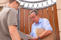 Postal service - delivery of a package. The postmen is giving the package to the customer in front of his house; the customer receipt the delivery stock image