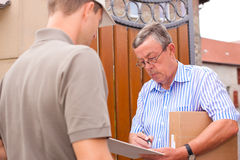 Postal service - delivery of a package. The postmen is giving the package to the customer in front of his house; the customer receipt the delivery stock photos