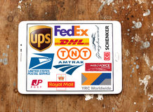 Postal shipping companies logos and vector. Collection of logos and icons of top postal shipping companies and services on white tablet on rusty wooden Royalty Free Stock Image