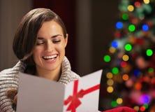 Postal sonriente de la lectura de la mujer delante del árbol de navidad Imagen de archivo