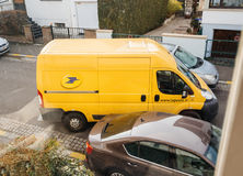 Postal van leaving after parcel delivery Royalty Free Stock Image