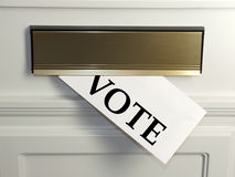 Postal Vote. A letter hangs out of a post box, with the word Vote written on the envelope royalty free stock photography