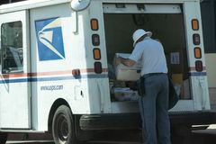 Postal worker at the back of truck with package. WASHINGTON D.C. - APRIL 12, 2018: President Trump issued an executive order creating a task force to evaluate Royalty Free Stock Image