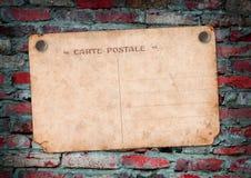 Postale della carta su un muro di mattoni Fotografia Stock