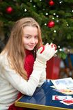Postales de la Navidad de la escritura de la muchacha en un café Imágenes de archivo libres de regalías