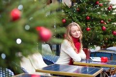 Postales de la Navidad de la escritura de la muchacha en un café Foto de archivo