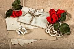 Postales, flor de la rosa del rojo, perfume y collar viejos de los perls Foto de archivo
