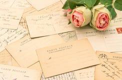 Postales francesas antiguas y flores color de rosa Foto de archivo libre de regalías