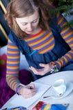Postales hermosas de la escritura de la muchacha en café Foto de archivo libre de regalías