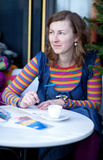 Postales hermosas de la escritura de la muchacha en café Fotos de archivo libres de regalías