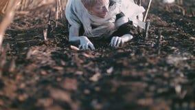 Postapocalypse 女孩爬行被烧焦的地球上 在烟和灰附近 股票录像