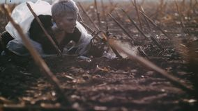 Postapocalypse das Mädchen kriecht auf die verbrannte Erde um Rauch und Asche stock video