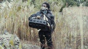 Postapocalypse, einsame junge Frau geht auf Feld mit Abfall in verlassener Stadt stock video footage