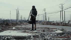 Postapocalypse, einsame junge Frau geht unter Müllkippe und verlassener Stadt stock footage
