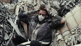 Postapocalypse, einsame junge Frau sitzt unter der Müllkippe, Ruinen stock footage