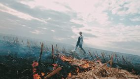 Postapocalypse. Girl on the scorched field. Around the fire and smoke