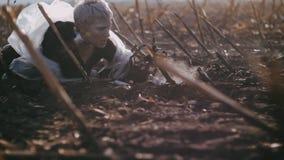 Postapocalypse het meisje kruipt op de geschroeide aarde rond rook en as stock video