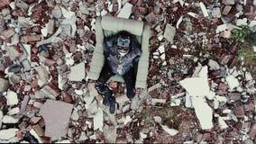 Postapocalypse, mujer joven sola se sienta en medio de los edificios destruidos, ruinas almacen de video
