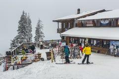 Postavaru瑞士山中的牧人小屋的滑雪者 库存图片