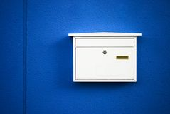 Postbox. White on a blue wall ,outdoor Stock Images