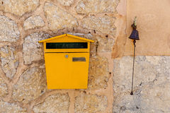 Postbox and a bell. Set in a stone wall Stock Photos