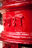 Postbox detail. Post and mail theme: close-up on red UK pillarbox. Selective focus. Portrait orientation Stock Photos
