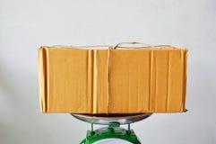 Postbox di Brown sul vassoio della bilancia in negozio Fotografia Stock