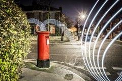 Postbox- och ljusslingor i London förort Arkivbild