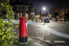 Postbox- och ljusslingor i London förort Royaltyfri Fotografi