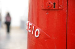Postbox. Red antique postbox and a blurred woman in background Royalty Free Stock Photo