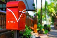 Postbox som är röd i trädgården Royaltyfri Bild